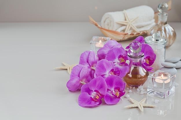 자주색 난초 꽃으로 둘러싸인 향수 또는 아로마 오일 병으로 스파 트리트먼트 구성