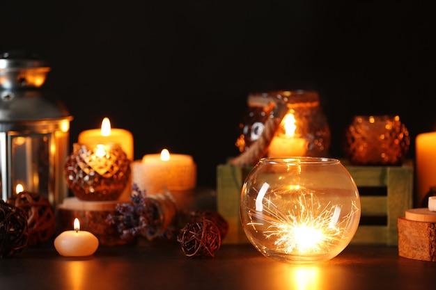 Композиция из бенгальского огня, стеклянной вазы и декора на темном фоне