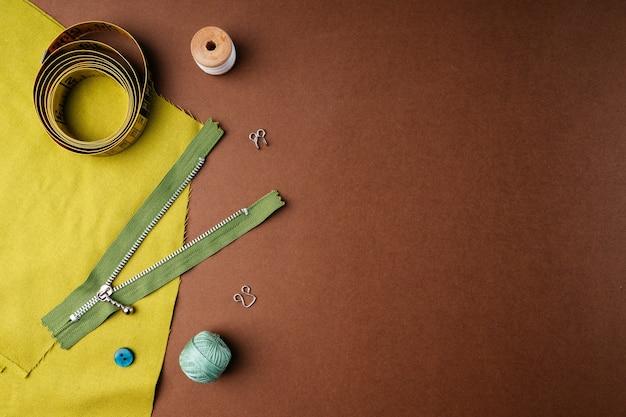 Композиция из катушек ниток и других швейных принадлежностей на коричневом фоне, плоская квартира, вид сверху