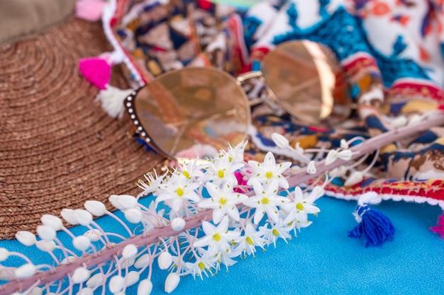 Композиция из шляпы от солнца, солнцезащитных очков, цветка и парео на синем пляжном полотенце