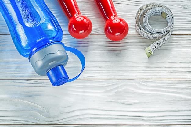 Композиция из рулетки с бутылкой с водой красных гантелей на деревянной доске
