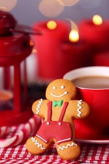 Композиция вкусного имбирного печенья и чашки кофе на кухонном столе, вид крупным планом