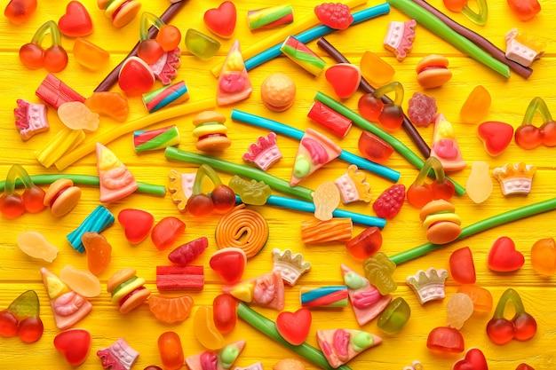 Композиция вкусных желейных конфет на фоне деревянного стола