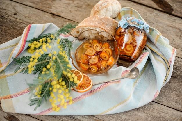 Состав засахаренной апельсиновой цедры спирали с сахарным сиропом в стеклянной банке и тарелке возле блюдца с грецкими орехами, мимозой и хлебом на салфетке на деревянном столе
