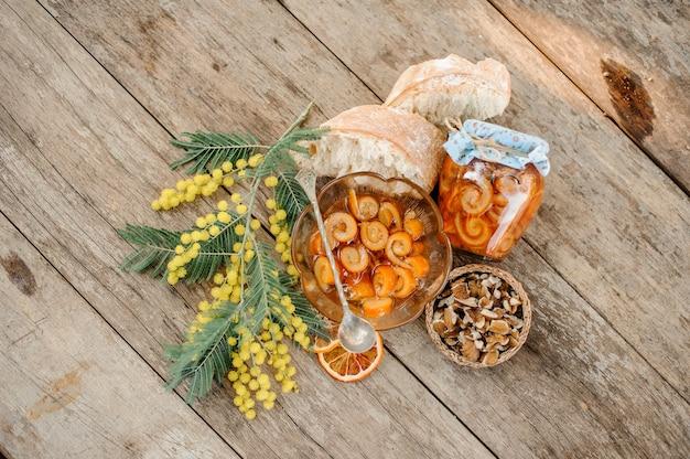 Состав засахаренной апельсиновой цедры спирали с сахарным сиропом в стеклянной банке и тарелке возле блюдца с грецкими орехами, мимозой и хлебом на деревянном столе