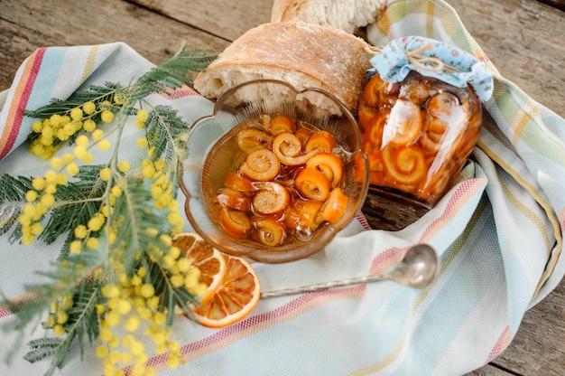 Состав засахаренной апельсиновой спиральной цедры с сахарным сиропом в стеклянной банке и тарелке возле блюдца с грецкими орехами, мимозой, ложкой и хлебом на салфетке на деревянном столе