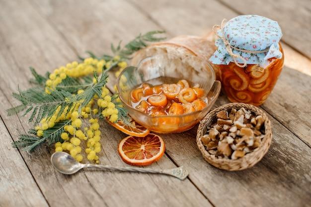 Состав засахаренной апельсиновой цедры спирали с сахарным сиропом в стеклянной банке и тарелке возле блюдца с грецкими орехами, мимозой, ложкой и хлебом на деревянном столе