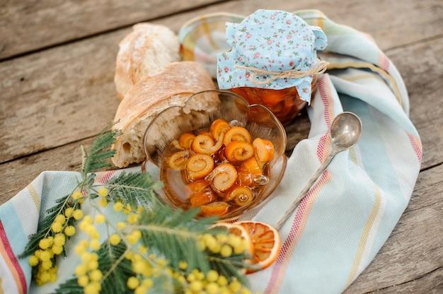Состав засахаренной апельсиновой спиральной цедры с сахарным сиропом в стеклянной банке и тарелке возле блюдца с грецкими орехами, веточкой мимозы, ложкой и хлебом на салфетке на деревянном столе