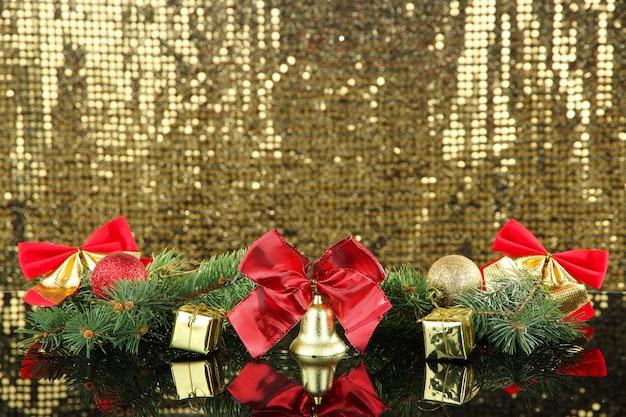 金色の表面のクリスマスの装飾の構成