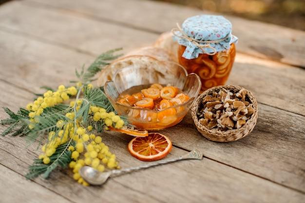 Композиция из вкусной цукаты из спиральной цедры апельсина с сахарным сиропом в стеклянной банке и тарелка возле блюдца с грецкими орехами, мимозой и хлебом на деревянном столе