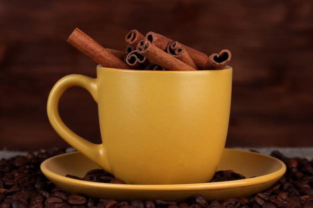 木製スペースにコーヒー豆とシナモンと黄色いカップの構成