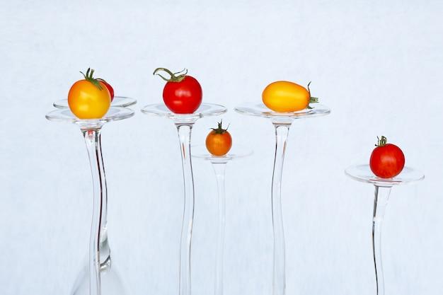 ワイングラスでさまざまなサイズと色のトマトの組成。