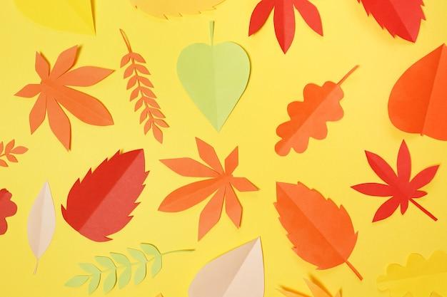 노란색 배경, 질감 있는 벽에 다양한 다채로운 잎의 구성