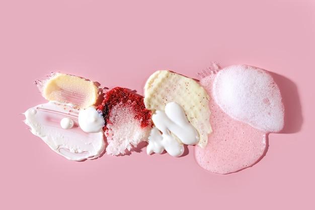 분홍색 배경에 다양한 화장품 마스크, 크림, 혈청, 스크럽, 로션 얼룩의 구성. 아름다움 질감입니다. 화장품 샘플입니다.