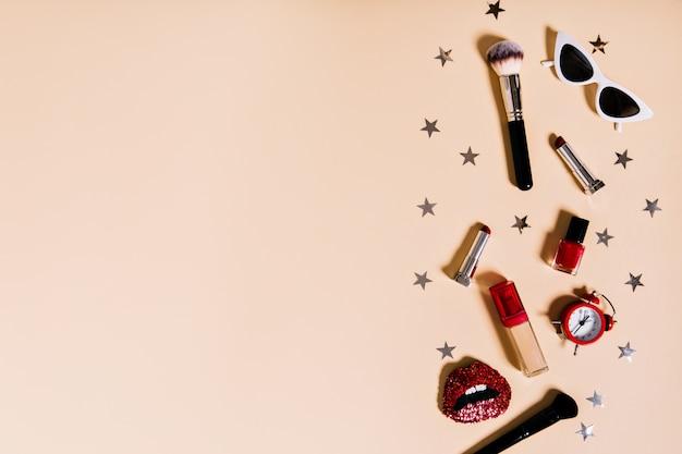 さまざまな化粧品の構成は、目覚まし時計や女性のアクセサリーと混合されています
