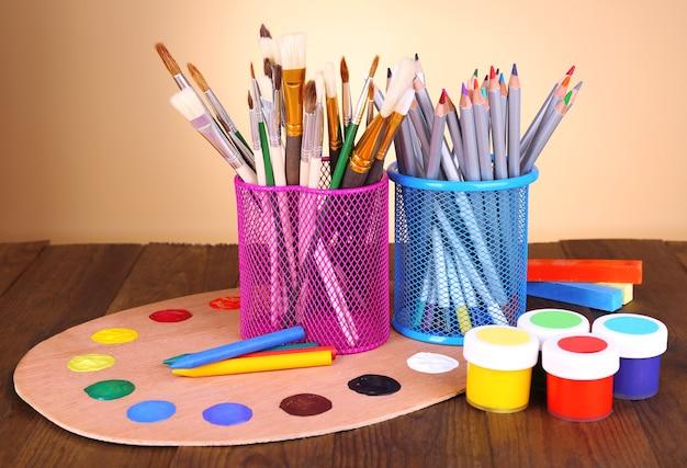 Состав различных творческих инструментов на столе на бежевом фоне