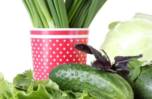 白い皿にさまざまなハーブを組み合わせ、白い接写に白い水玉模様の赤いカップ