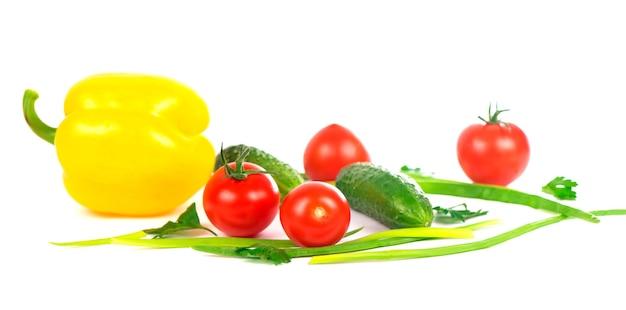 Композиция из овощей на белом фоне помидоры, огурцы и зеленый лук