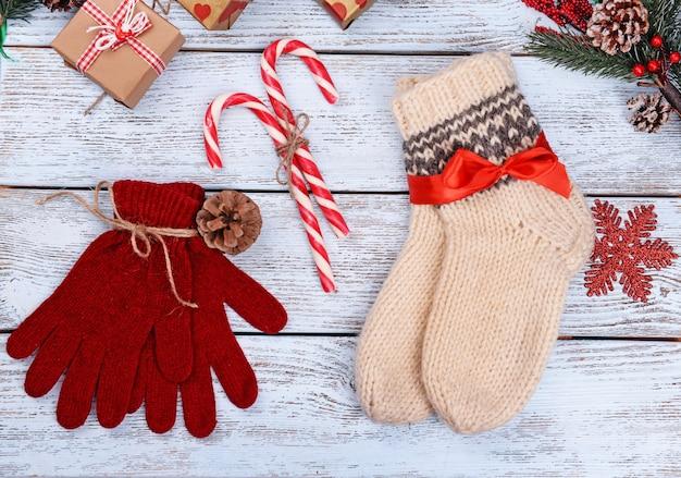 白い木製の背景にクリスマスの装飾と暖かい靴下と手袋の構成