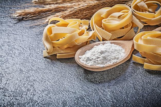 黒い背景に小麦ライ麦耳木のスプーン小麦粉パスタフェットチーネの組成物。