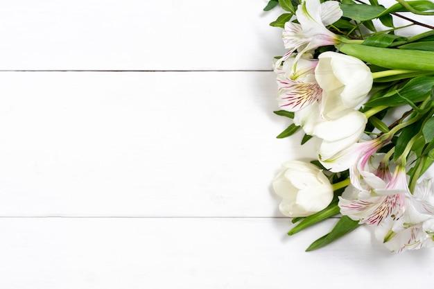 복사 공간 흰색 나무 배경에 흰색 꽃의 구성. 휴일 및 축하 개념