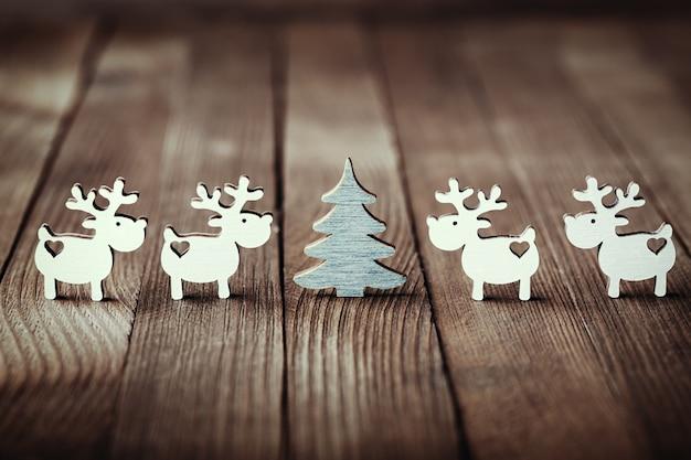 木製のテーブルの上の白いトナカイとクリスマスツリーの構成。