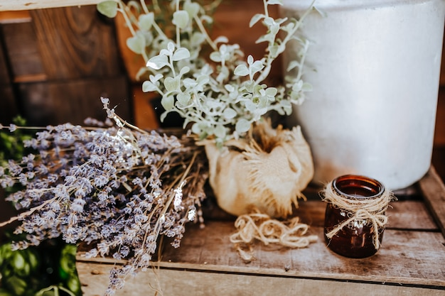 Композиция деревянного деревенского кухонного стола на открытом воздухе с декором из растений лаванды, овощей. загородный дом летом