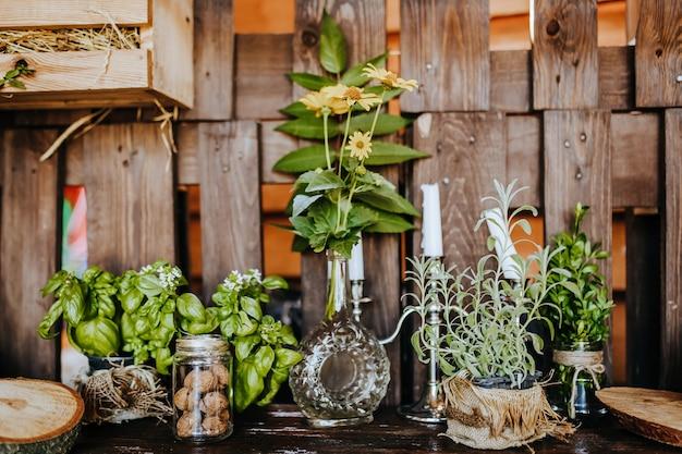 Композиция деревянного деревенского кухонного стола на открытом воздухе с декором из растений, овощей. загородный дом летом