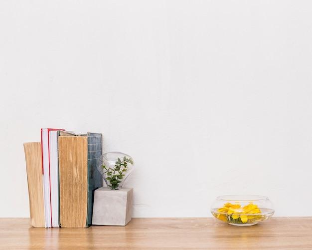 Композиция из желтых зеленых растений и книг на столе