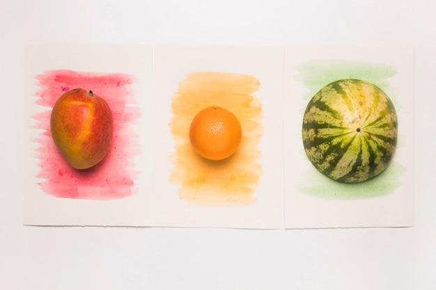 Композиция из вкусных цельных смешанных фруктов на разноцветной акварельной поверхности