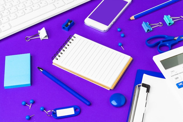 Composition of office lifestyle items on  purple , computer keyboard office supplies on desk in office