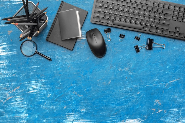 Composition of office supplies and equipment in black and blue background, top view
