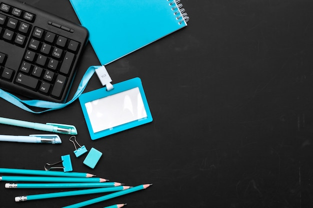 Composition of office supplies and equipment in black and blue colors background, top view