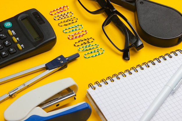 Composition of office tools, stationery on yellow