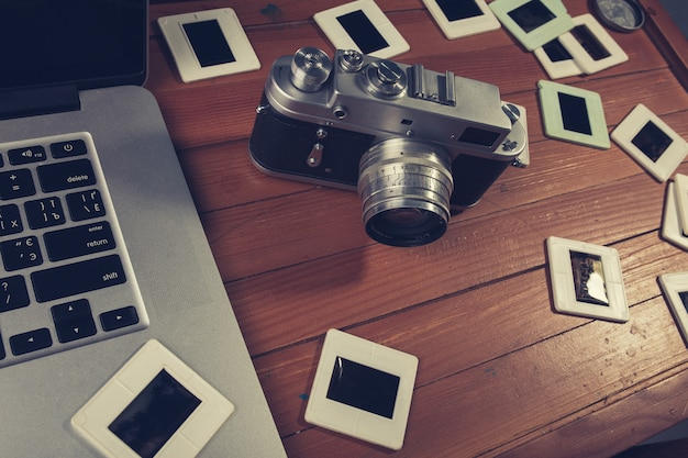 Composition of old photo camera, laptop and slides