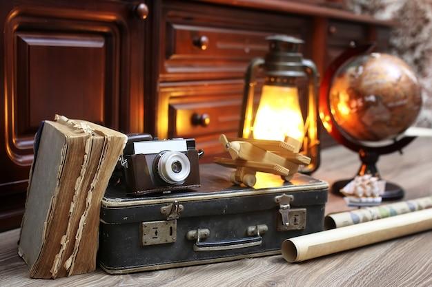 旅行用のオブジェクトが付いている古い革のスーツケースが付いている木の床のビンテージ地球儀の構成