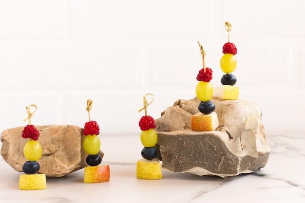 Композиция на фоне белой кирпичной стены фруктовых канапе. вкусный летний десерт. здоровое питание.