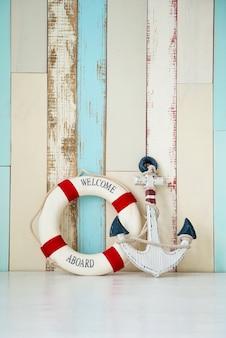 木製の背景にアンカーとライフラインを備えた海洋をテーマにした構成。