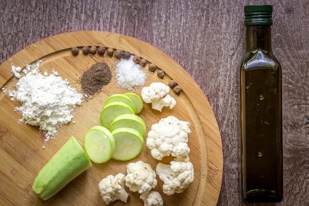 Композиция на деревянных фоне органических вегетарианских продуктов: цукини, цветная капуста, черный перец, пшеничная мука и соль. вид сверху. скопируйте место для вашего текста