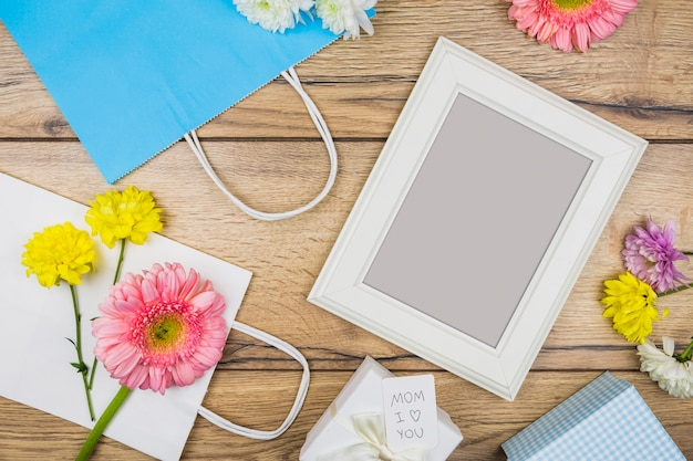 Composition of photo frame near fresh flowers, present boxes and paper packets