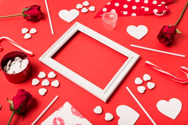 Composition of photo frame between paper hearts, flowers and wands