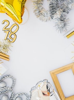 Composition of photo frame, tinsel, 2019 numbers and balloon