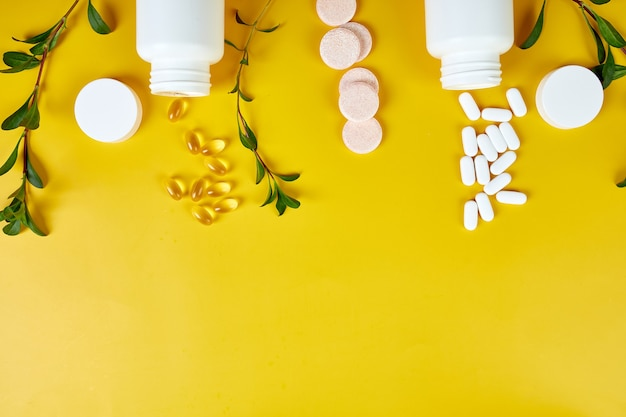 Composition of pills, fish oil, vitamins with green leavws on yellow surface