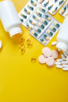 Composition of pills, fish oil, vitamins on yellow surface
