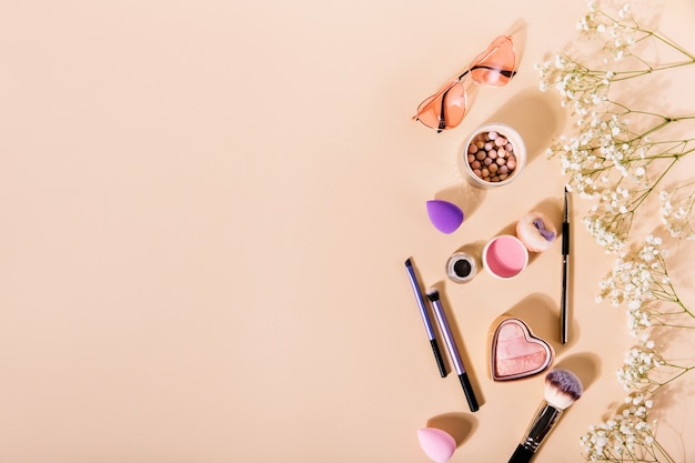 Composition of pink blush, makeup brushes and glasses in shape of hearts lies among cute flowers