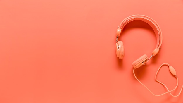 Composition of pink headphones with usb wire