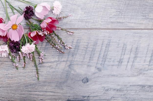 Композиция розовые фиолетовые цветы на деревянных досках. полевые цветы на фоне деревянного стола ручной работы. фон с копией пространства, плоская планировка, вид сверху. матери, валентинок, женщин, концепция дня свадьбы.
