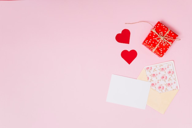 Composition of present box near ornament hearts and envelope
