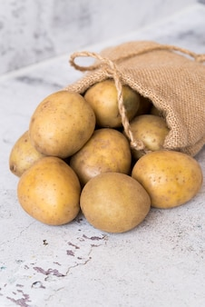 Composition of raw potatoes in bag on cement background