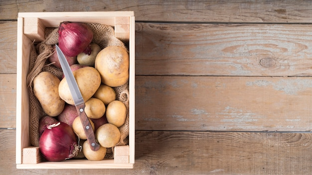 Composition of raw potatoes in wooden box with copy space